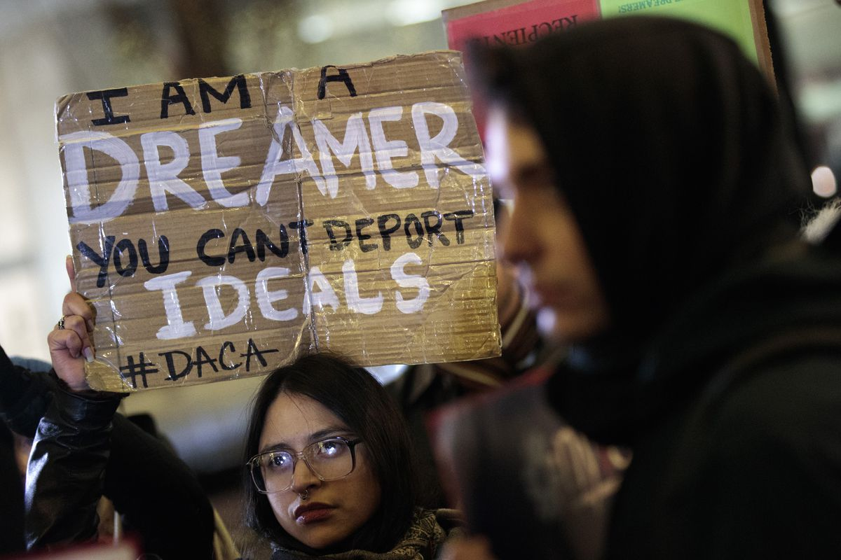 """An immigration activist holds a sign that reads, """"I am a Dreamer. You can't deport ideals. #DACA."""""""