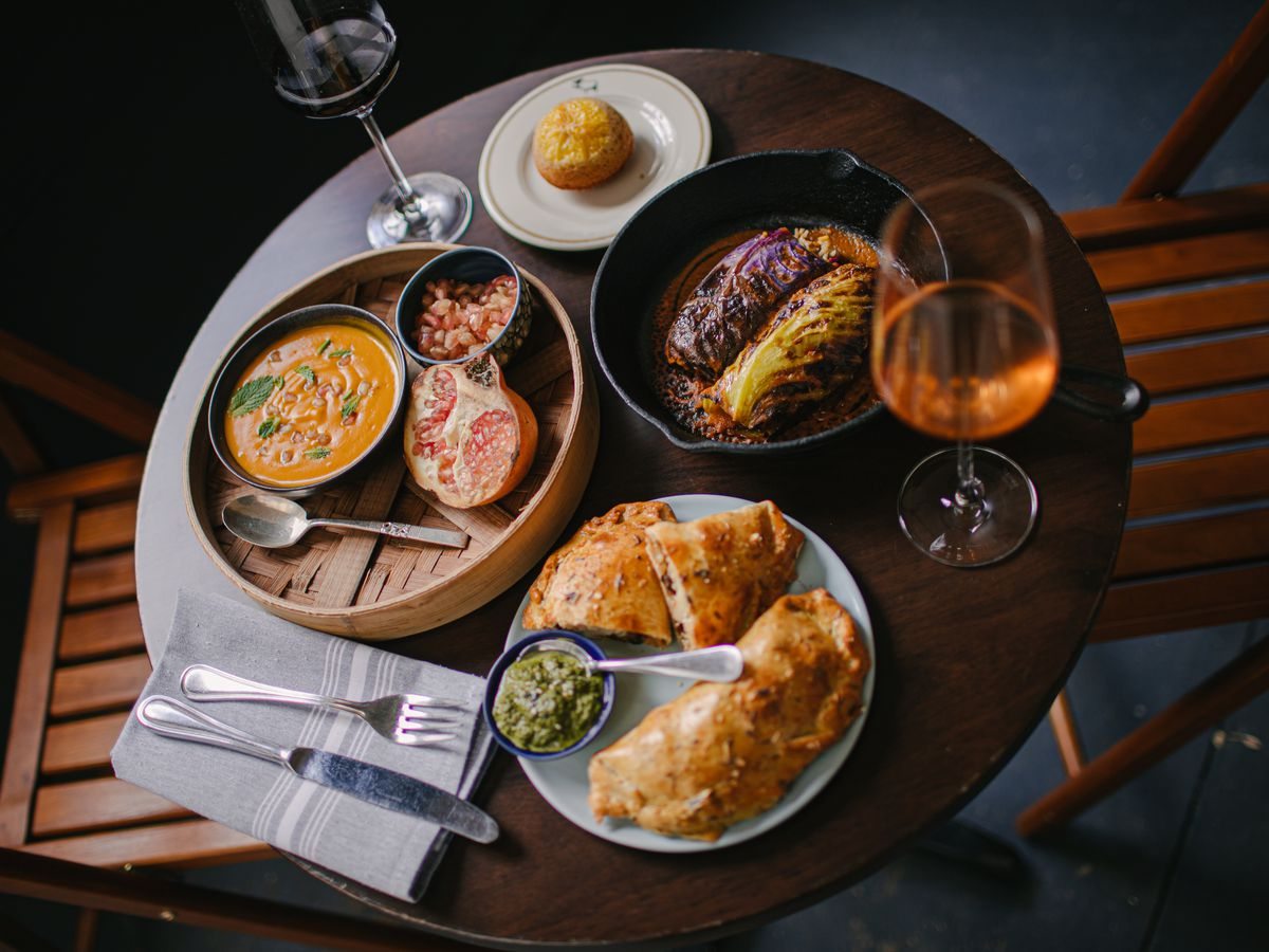 A table is set with several bowls, which contain empanadas, grilled cabbage, and an orange soup