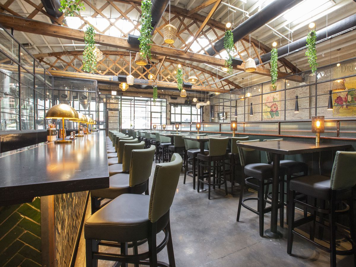 A high-ceilinged brewpub dining room with high-top tables and chairs.