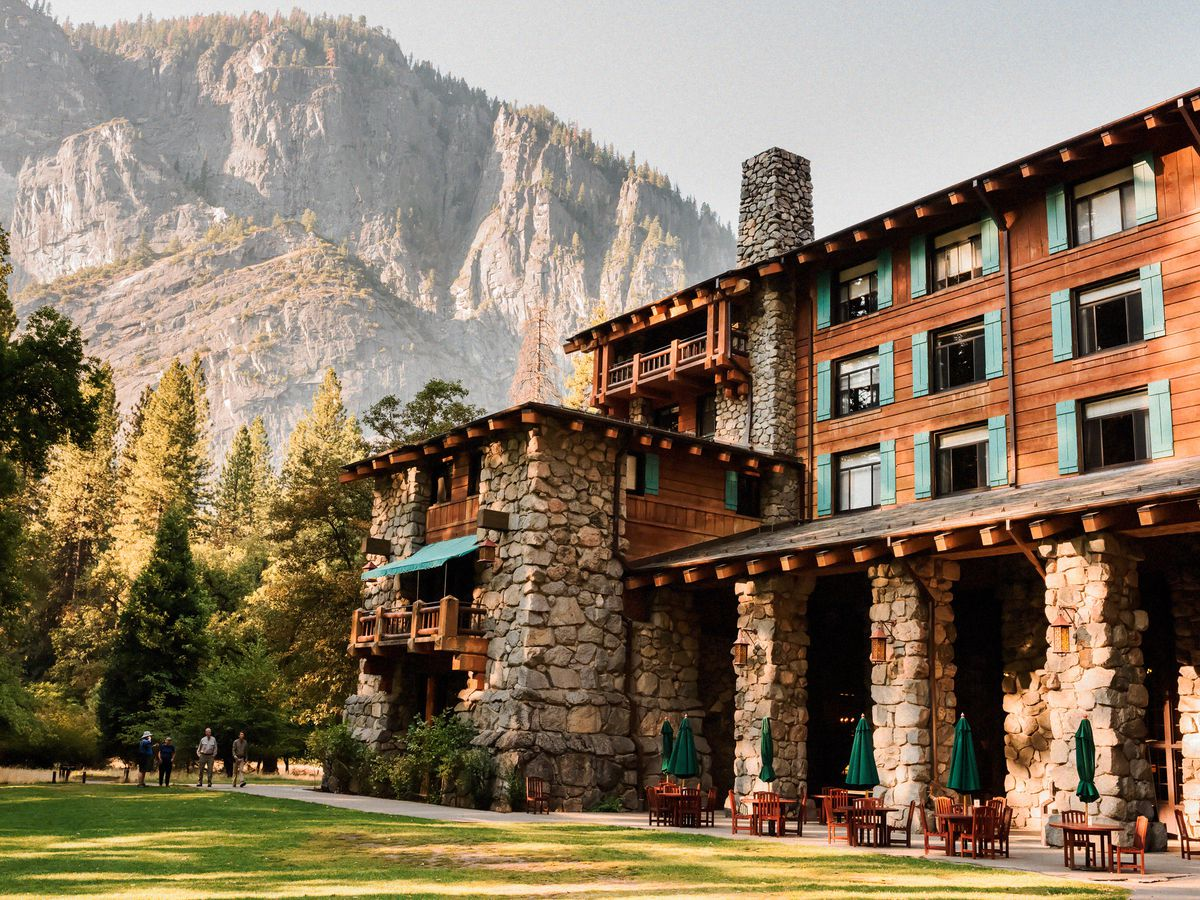 The exterior of the Majestic Yosemite Hotel. The facade is red brick and stone with columns. There are mountains and trees in the background.
