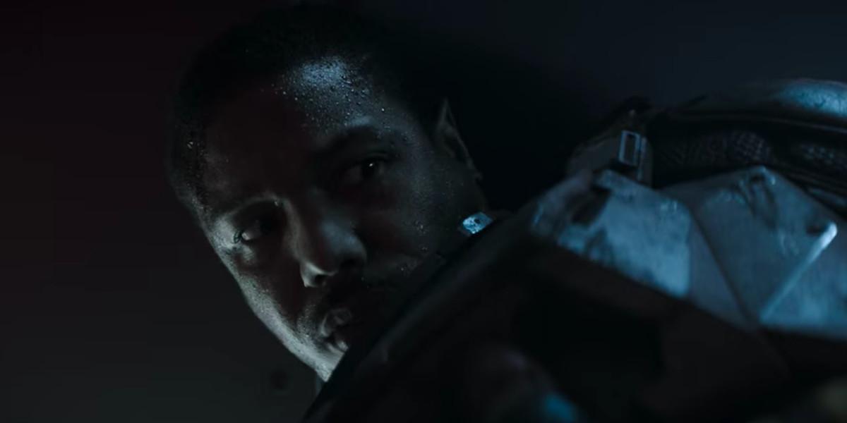 a man in futuristic looking armor looks very tense