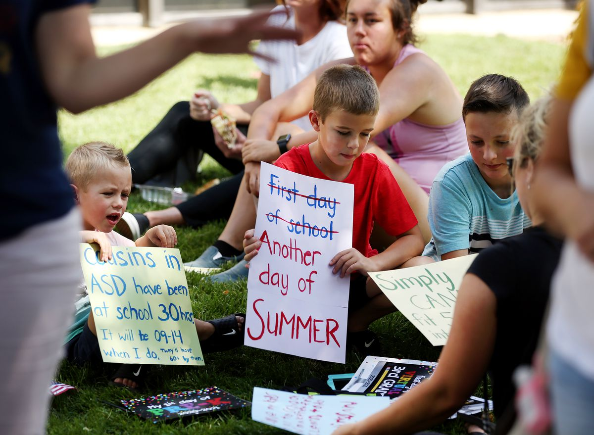 Kole Butler, left, Jace Butler and Tyke Butler look at signs as students and parents hold a sit-in at the Davis School District offices in Farmington on Tuesday, Aug. 25, 2020. The group was protesting the district's hybrid schedule of online and in-person learning.