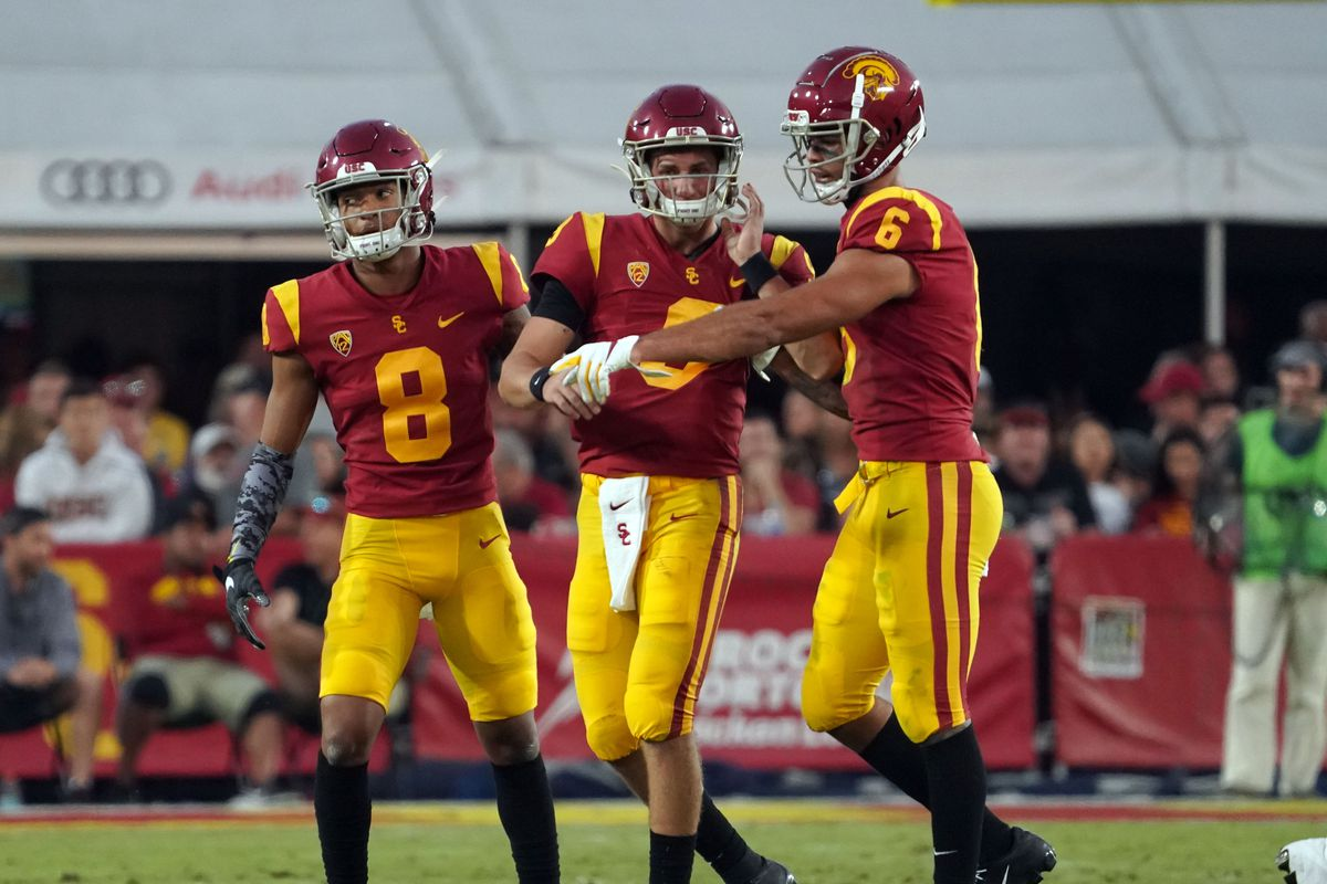 USC Trojans quarterback Kedon Slovis, center, is helped to the sideline by wide receivers Amon-Ra St. Brown and Michael Pittman Jr. after taking a late hit at the Los Angeles Memorial Coliseum on Saturday, Nov. 2, 2019.