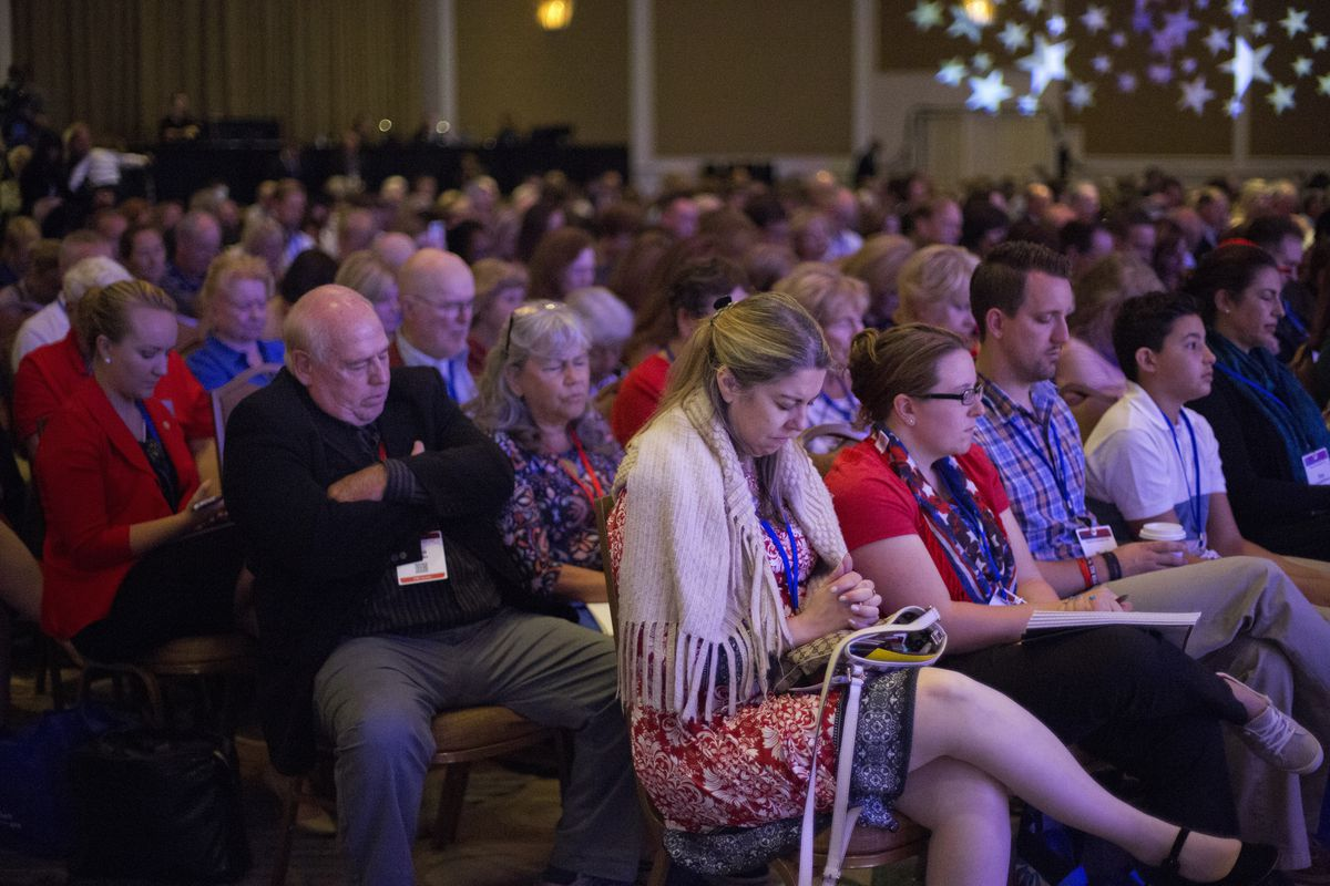 Attendees lower their heads for a prayer at the opening ceremonies at the 2018 Values Voters Summit in Washington, Friday, Sept. 21, 2018.