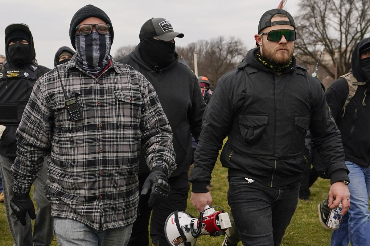 In this Jan. 6, 2021, file photo, Proud Boys members Joseph Biggs, left, and Ethan Nordean, right with megaphone, walk toward the U.S. Capitol in Washington. A federal judge has ordered Biggs and Nordean, two leaders of the far-right Proud Boys extremist group, to be arrested and jailed while awaiting trial on charges they planned and coordinated an attack on the U.S. Capitol to stop Congress from certifying President Joe Biden's electoral victory.