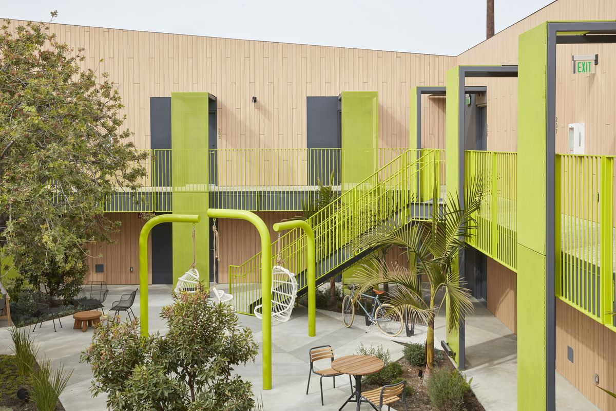 A photo of the shared courtyard at the Mayumi, which features bright green metal railings and outdoor furniture.