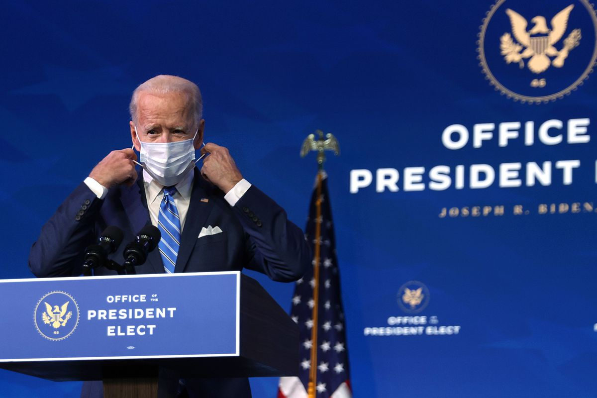 President-Elect Biden stands behind a podium as he prepares to take off a blue mask