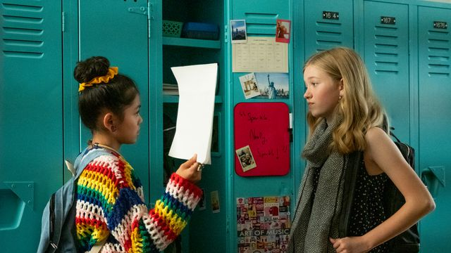 Two of the babysitters talk in front of a bright blue bank of school lockers in Netflix's The Baby-Sitters Club.