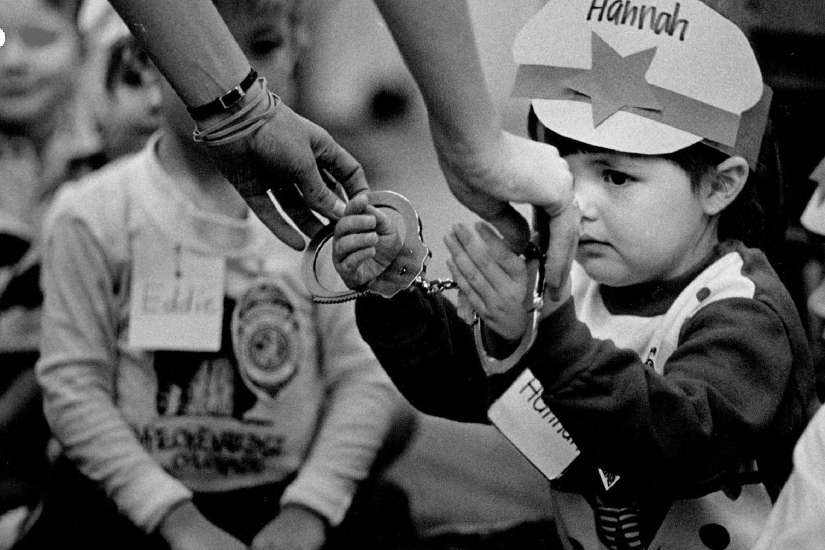A police officer handcuffs a child during a safety demonstration.