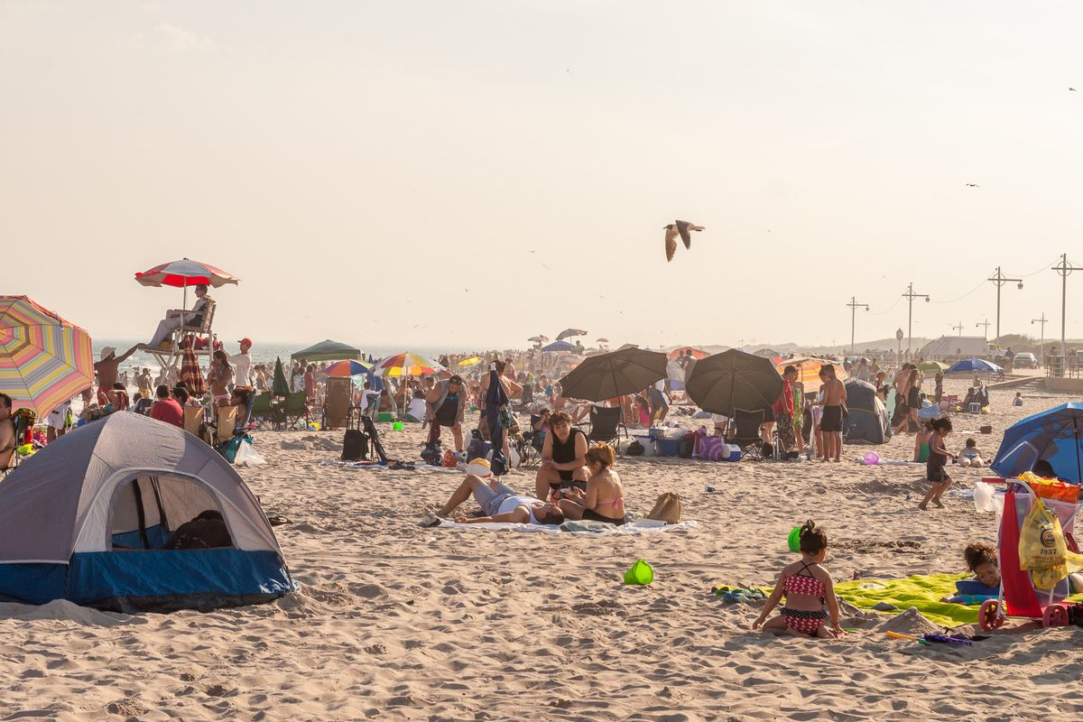 A sandy beach. There are beach tents, beachgoers, and colorful umbrellas on the beach.