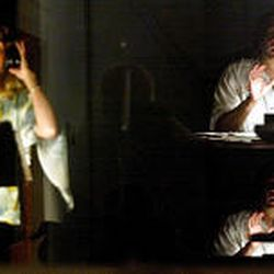 Reflected in the studio glass, Kurt Bestor works with singer Jonelle Goddard during a recording session at Studio 1 in Midvale. Over the years, Bestor has produced 22 CDs, with both Christmas and non-Christmas themes.