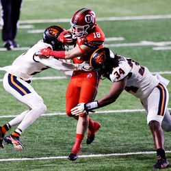 Utah Utes wide receiver Britain Covey (18) tries to split Oregon State Beavers defensive back Nahshon Wright (2) and Oregon State Beavers linebacker Avery Roberts (34) Utah and Oregon State play a college football game at Rice-Eccles Stadium in Salt Lake City on Saturday, Dec. 5, 2020.