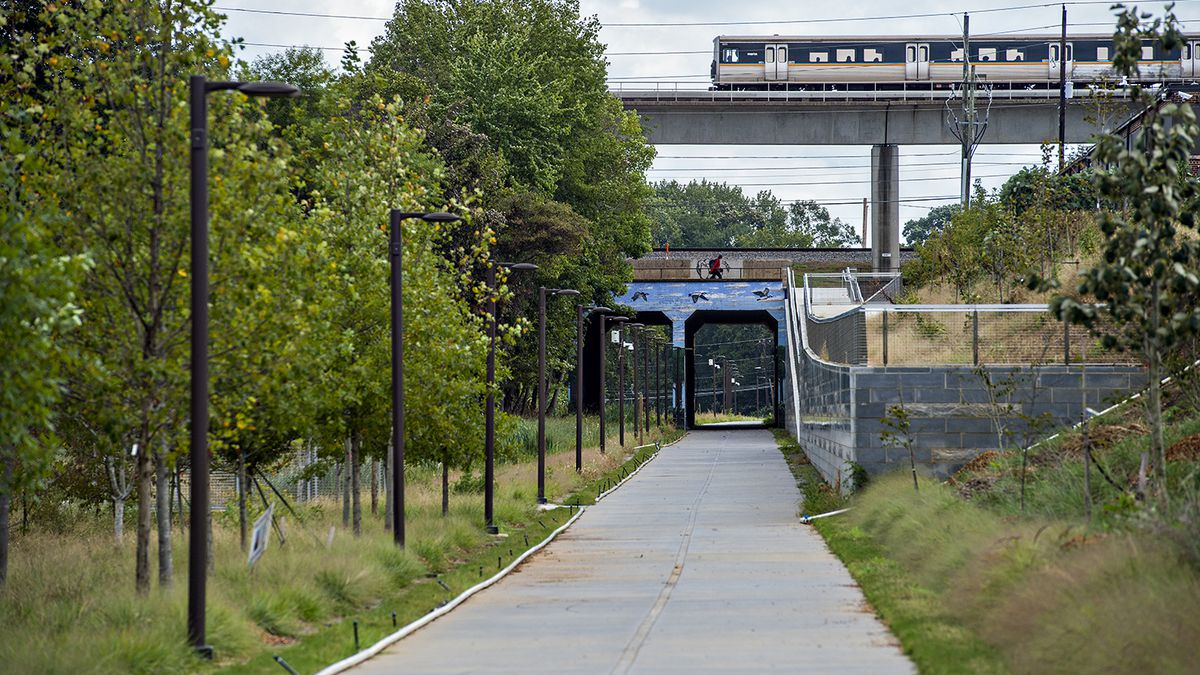 A MARTA train travels over a bridge and a pedestrian path with a bright blue tunnel that travels down a leafy green meadow dotted with trees. It is Atlanta's BeltLine.