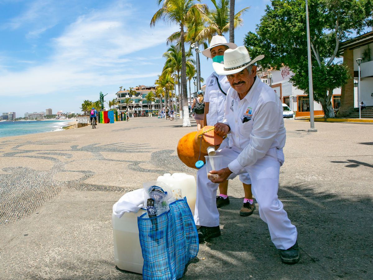 a man in white pours liquid from a large gourd.
