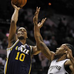 Utah Jazz guard Alec Burks, left, shoots against San Antonio Spurs forward Kawhi Leonard during the first half of an NBA basketball game, Wednesday, Jan. 15, 2014, in San Antonio. (AP Photo/Darren Abate)