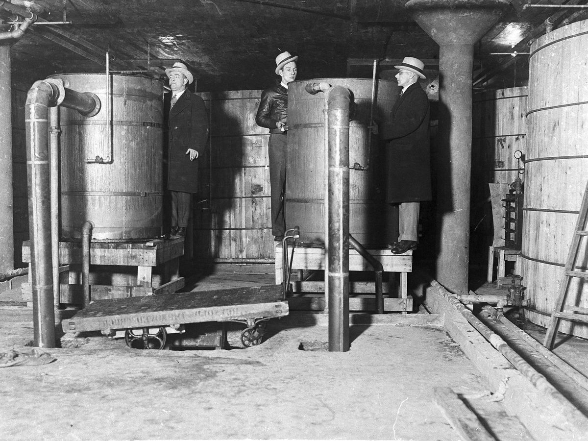 A black and white photo of three men in trench coats and fedoras next to big barrels.
