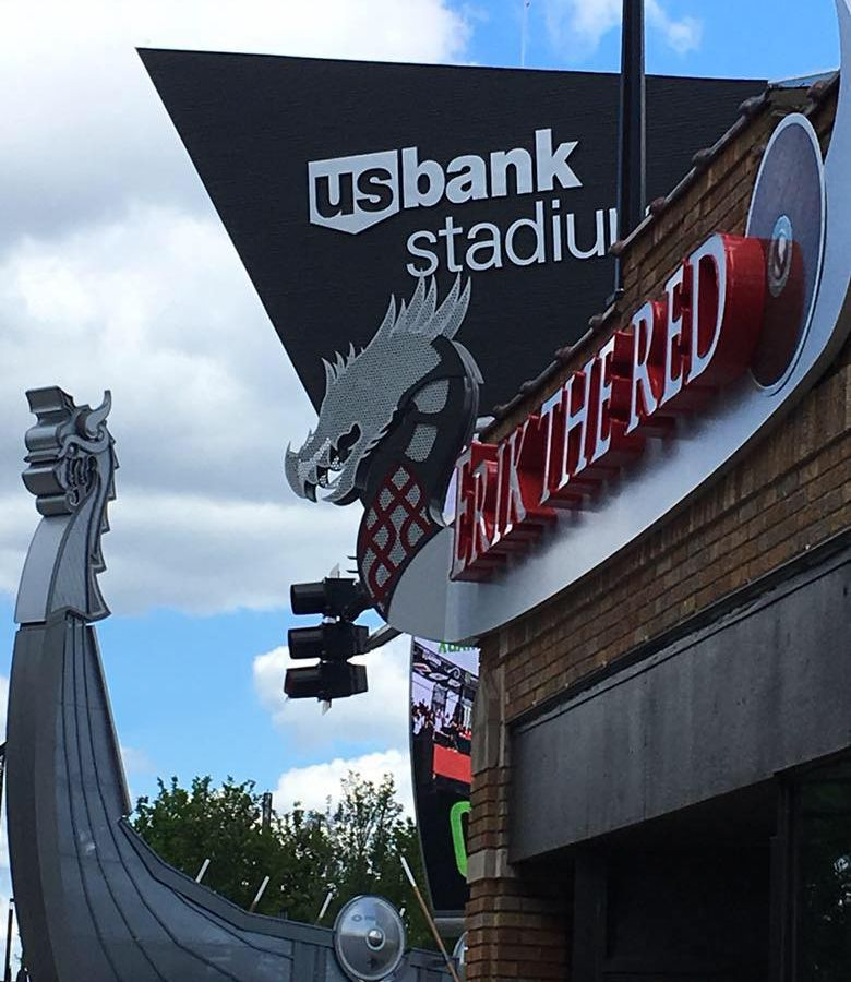 A viking ship outline backs the Erik the Red sign, US Bank stadium peeks out in the background