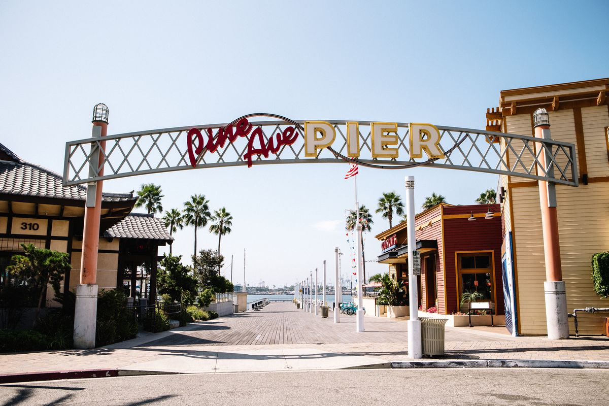 """A large metal sign that reads: """"Pine Avenue Pier."""" In the background is a mock-Japanese-style building, a red-colored restaurant, and a waterfront area"""
