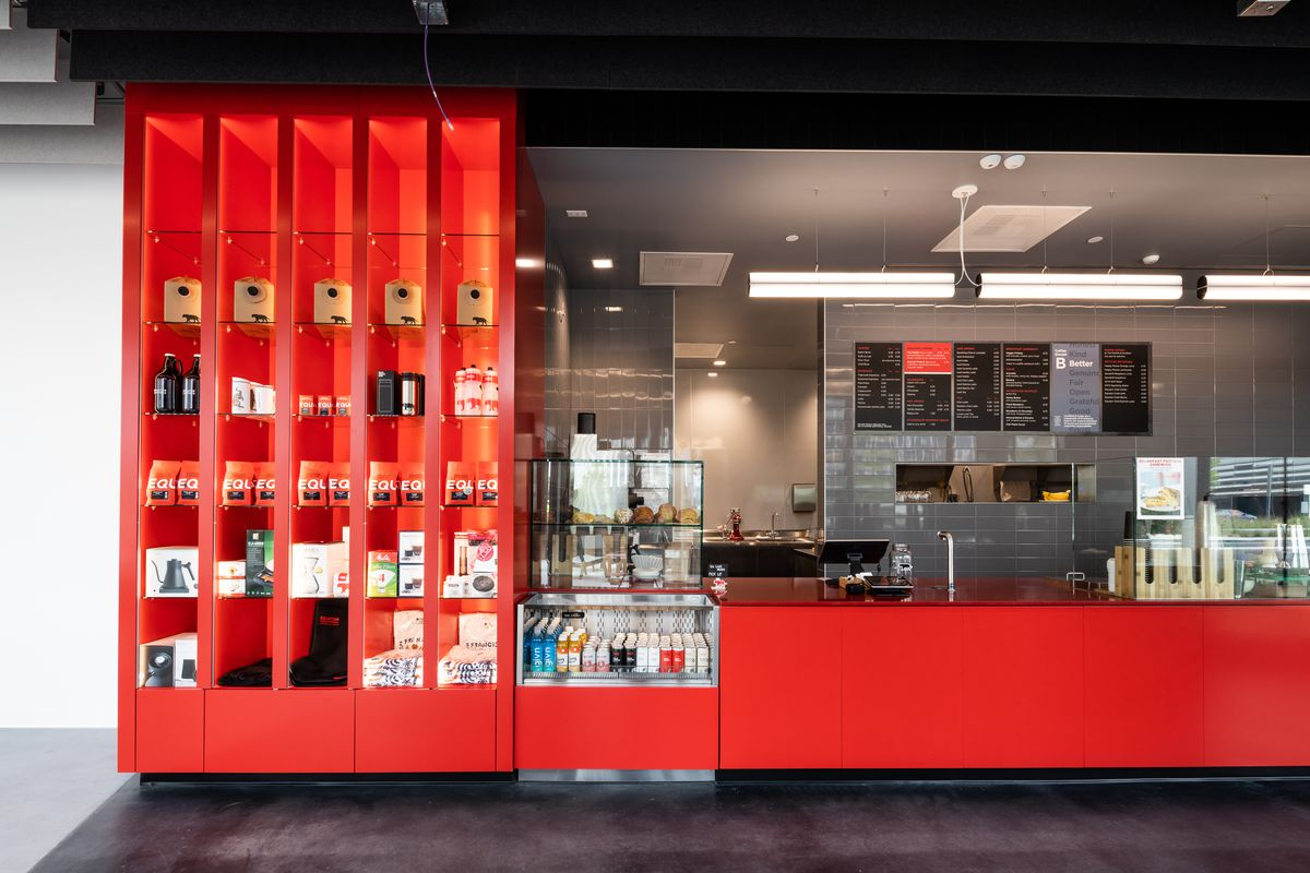 Inside Equator Coffee in Burlingame with red and black design and bags of coffee on shelves.