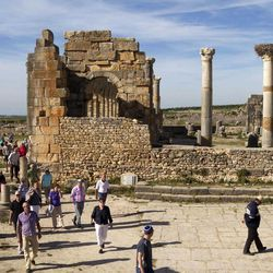 In this Thursday, March 8, 2012 photo, tourists gather around the arches of the Basilica, the main administrative building of Volubilis, Morocco's most famous Roman ruin near Meknes, Morocco. The site of Volubilis is one of the best preserved sites in Morocco and most visited.