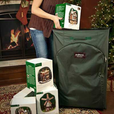 A large green holiday decoration storage case in front of a Christmas tree.