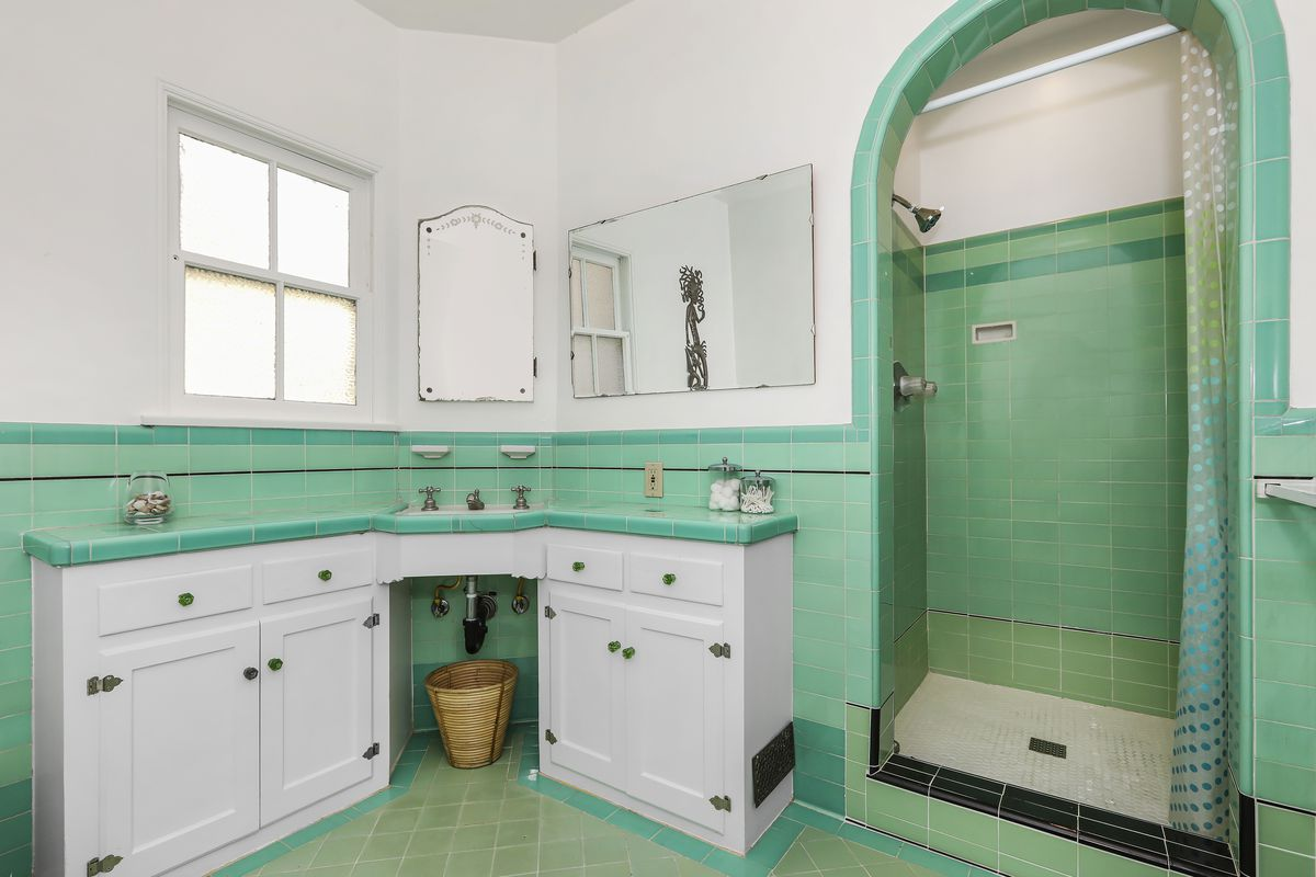 A sink and vanity alongside a shower with an arched frame, all partly covered with blue-green tile