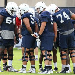 UConn's offensive line huddles during UConn Huskies football practice on Saturday, August 7, 2021
