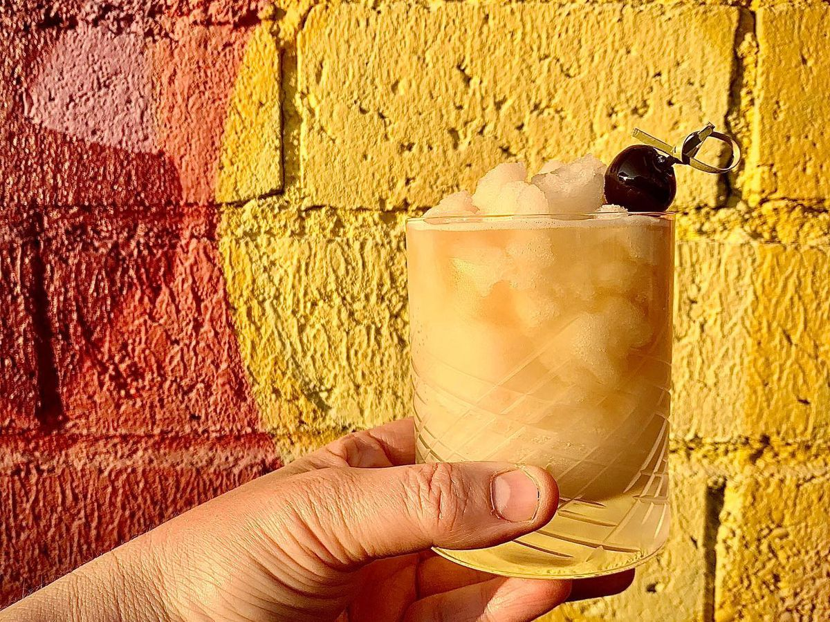 A Jammyland Rangoon gimlet held in a hand against a yellow and red brick wall.