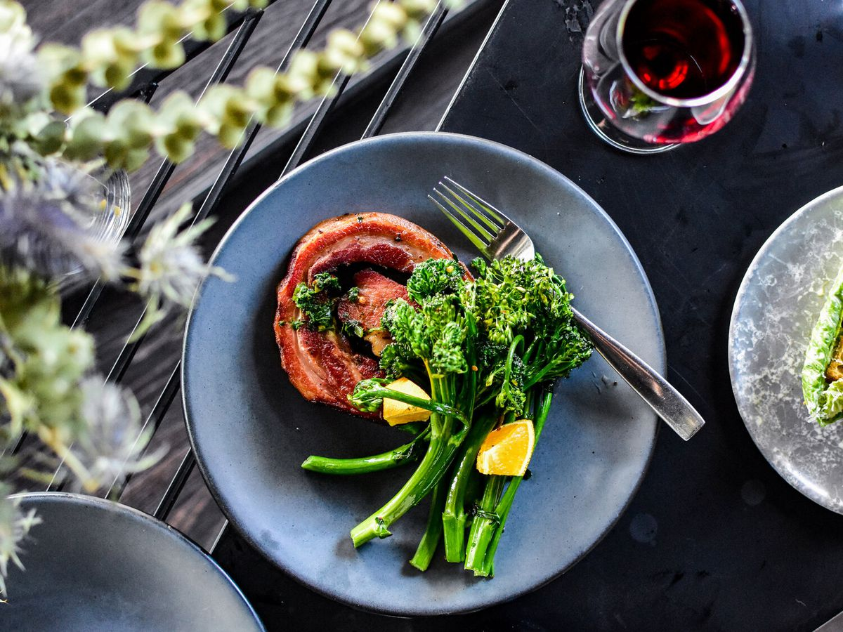 A gray plate with a round piece of brown meat and several stalks of broccolini with a fork.