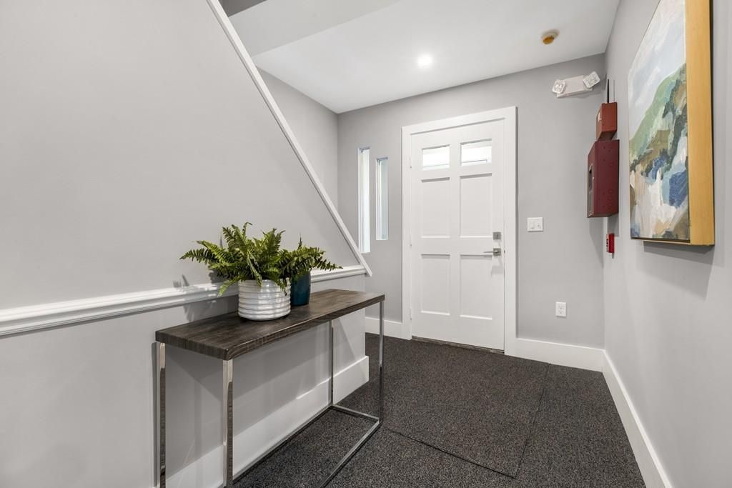 The entry foyer of a condo, with stairs leading up from it and the front door closed.