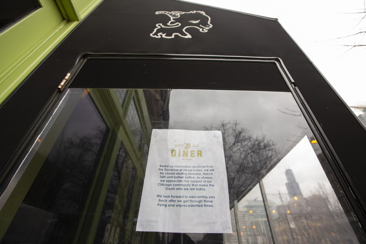 A white paper sign hangs in the window of a restaurant.