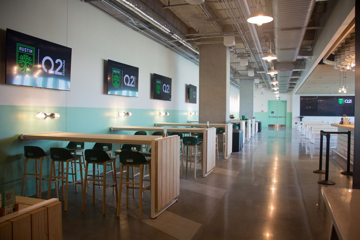 """An inside beer hall with long tables and television screens with Austin FC's logo and stadium name """"Q2"""""""