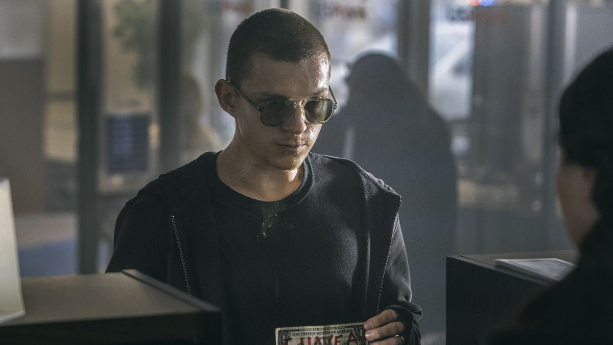 """Tom Holland as Cherry with a shaved head standing at a bank teller window with a dollar bill that says """"I have a gun"""" in red marker"""