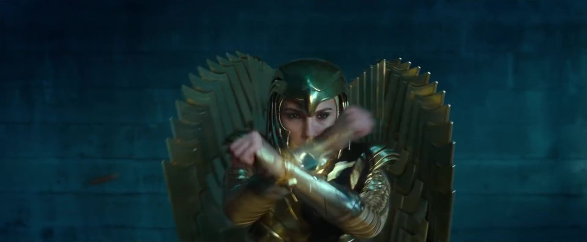 Gal Gadot as Diana blocks a bullet in her gold eagle armor, in Wonder Woman 1984.