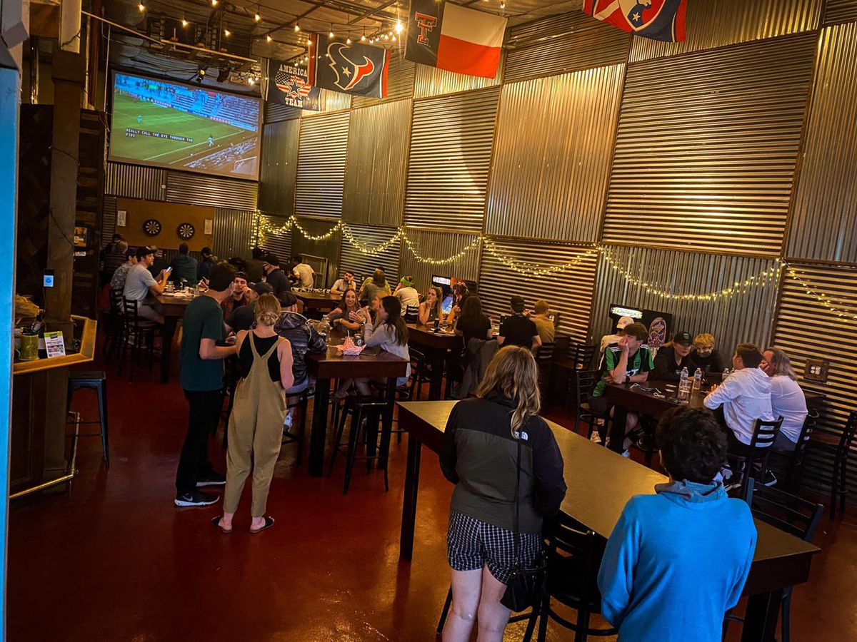 People standing and seating in groups in a large brewery taproom space with a projection screen showing a soccer game