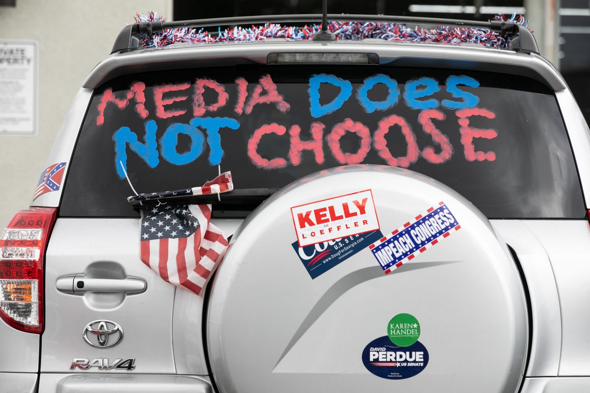 "The back of a car with ""Media does not choose"" written on the rear window and a Kelly Loeffler campaign sticker."
