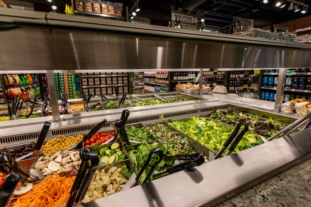 A salad bar under low lighting with black spoons hanging out of each metal tray.