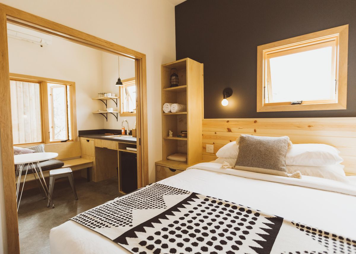 Large hotel room with wooden built-in shelves and tables.