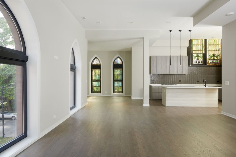 An open, unfurnished living space has a gray kitchen with three pendant lights and an island. The room has white walls, wood floors, and a mix of clear and stained glass windows.