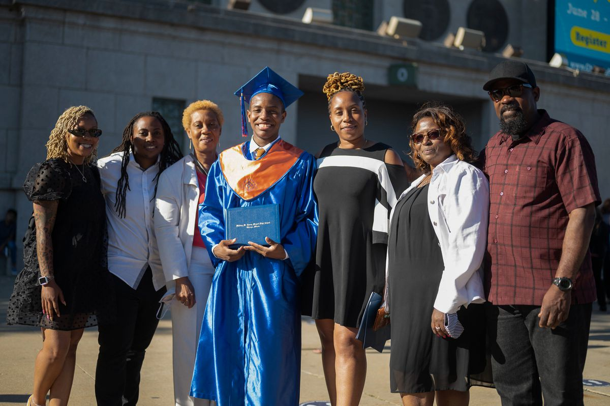 A family of seven pose for a group portrait around their new high school graduate, a young man who is wearing a blue and orange graduation cap and gown.