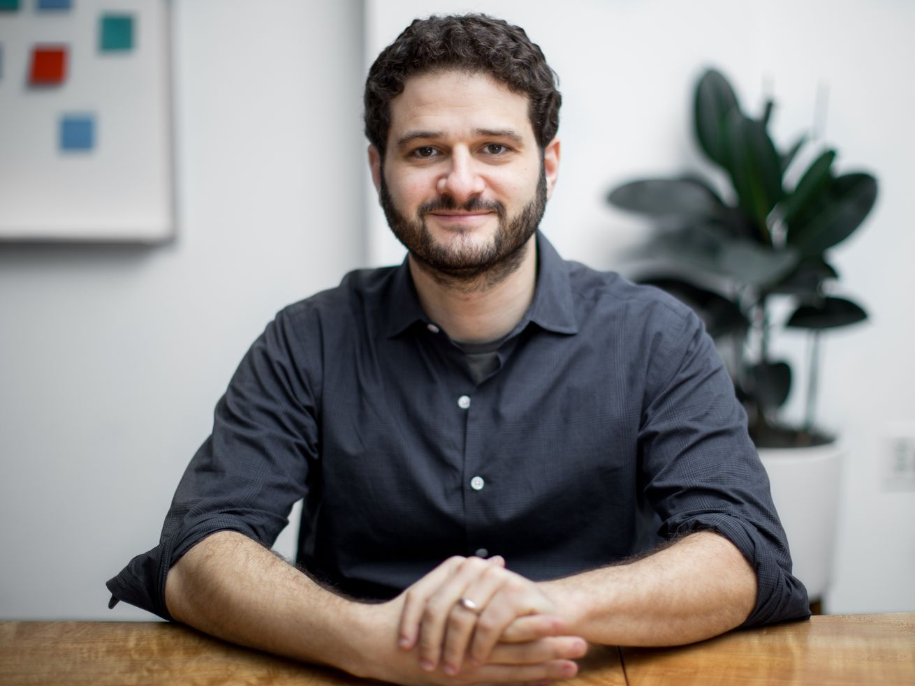 Dustin Moskovitz poses with his hands clasped on a table.