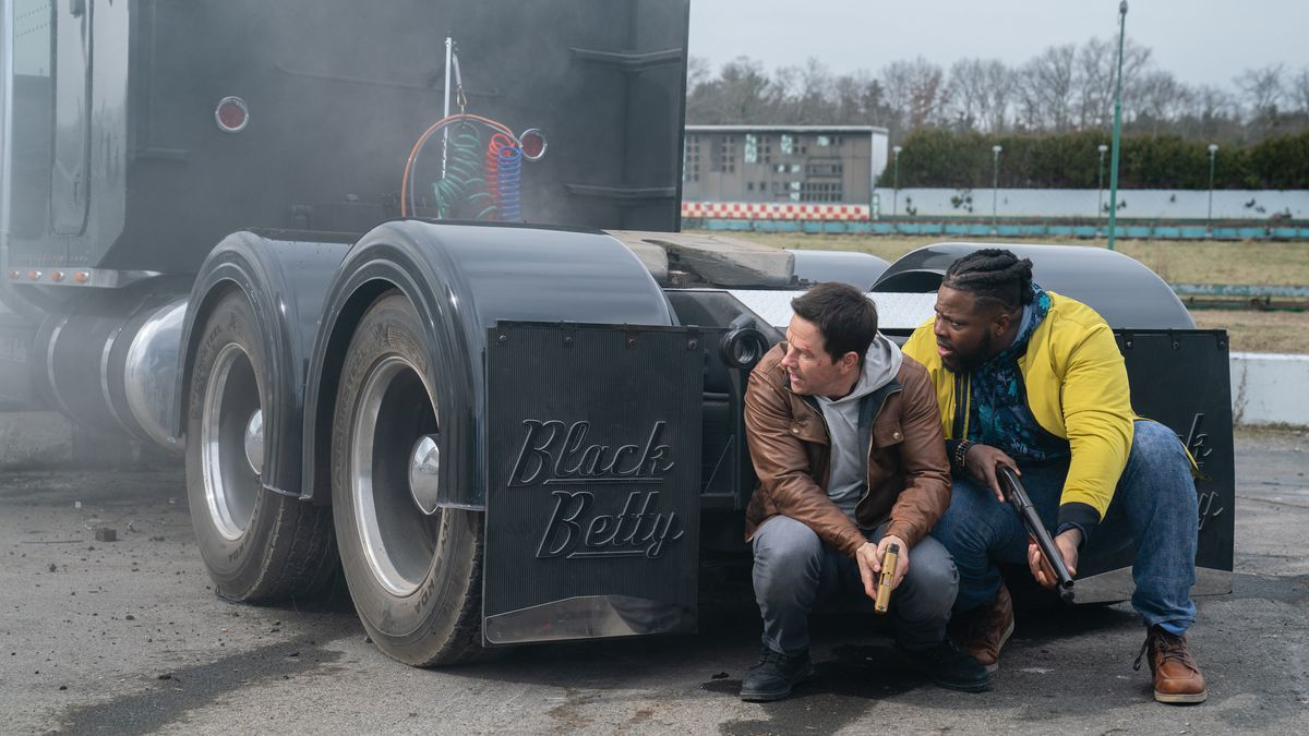 Two men crouch behind a truck.