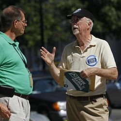 In this photo taken Sept. 26, 2012, volunteer Douglas Johnston, right, speaks with a pedestrian as he and other volunteers from a local campaign field office register voters in Raleigh, N.C. Dozens of volunteers armed with clipboards and voter registration forms gather at President Barack Obama's field office here every day. Their mission: Fan out across the city seeking new voters in this rapidly growing state.