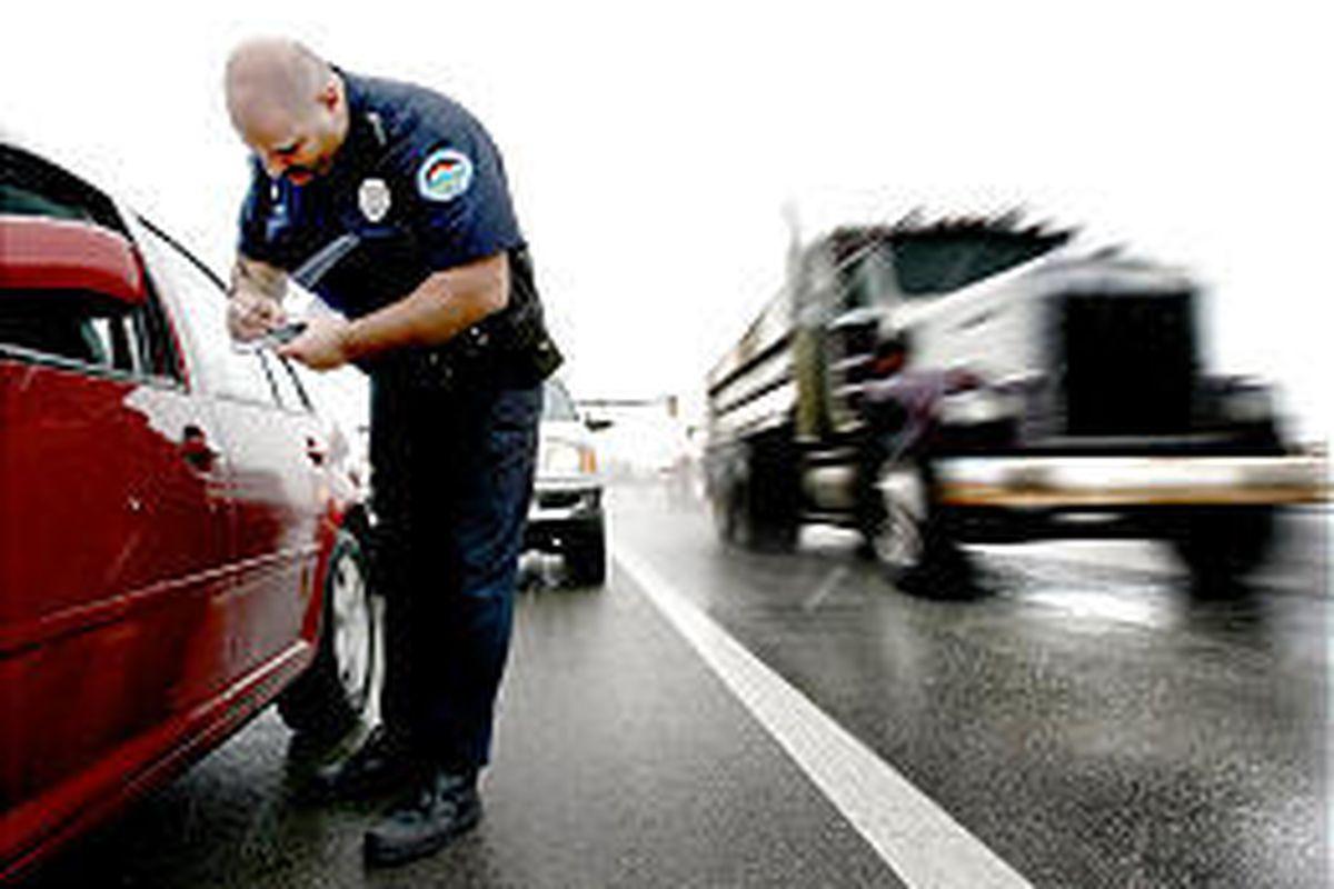 South Jordan police officer Samuel Winkler tickets a motorist. A bill would ban traffic ticket quotas.