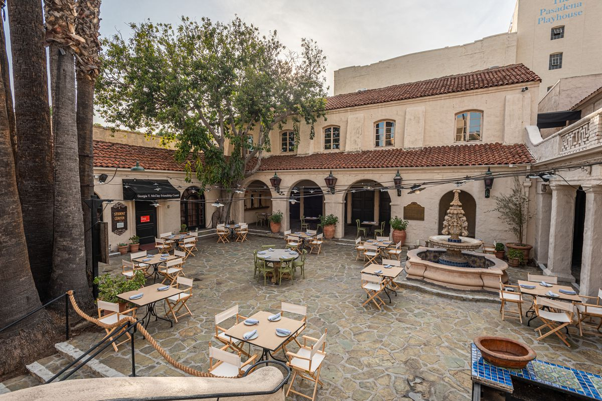 Distanced tables on a large stone patio in front of a restaurant.