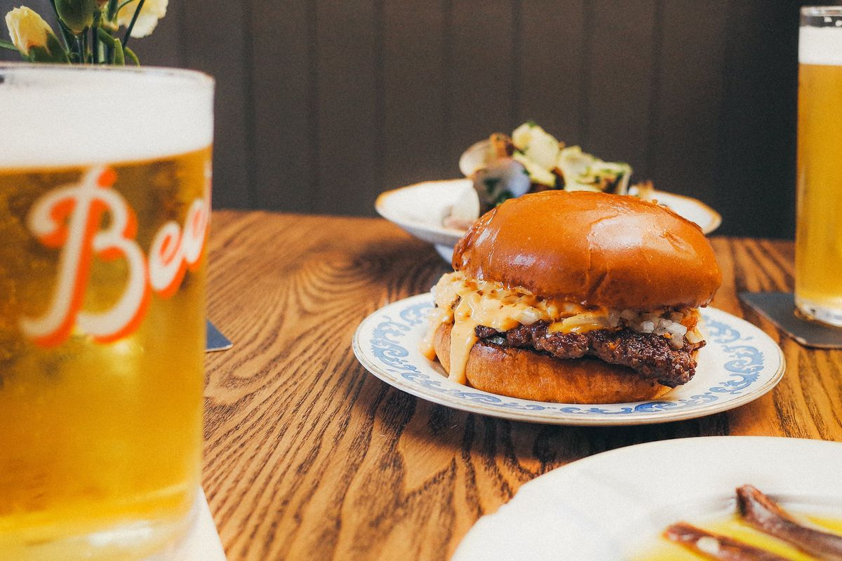 A cheeseburger on a blue-floral edge plate, with pints of beer surrounding it on a wooden table