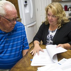 Frank Arnold Horton and his daughter, Suzanne Rengers, look over paperwork regarding their fraud case in West Jordan on Tuesday, Sept. 27, 2016. Horton and Rengers say they were both scammed by their tax preparer and financial manager last year.
