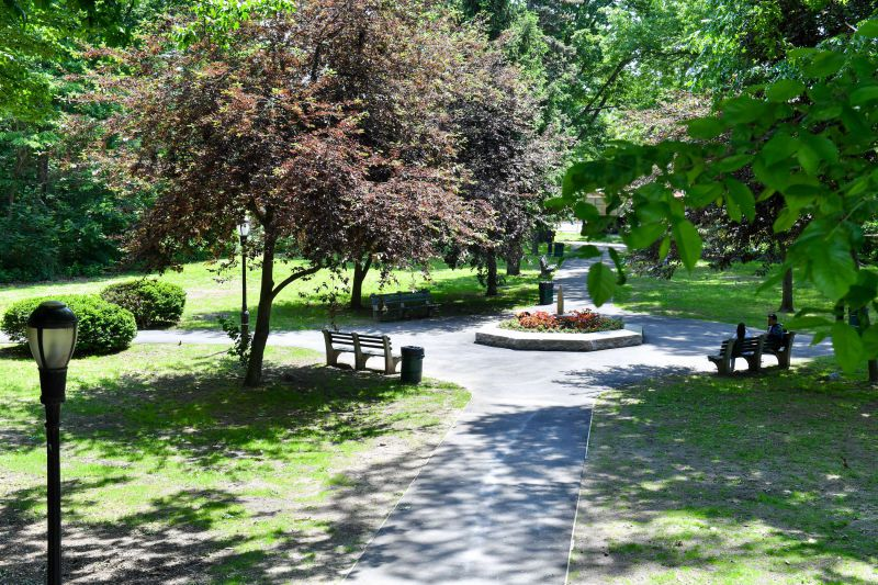 Stone benches line a paved circle path. Grass lawns and trees surround the walkway.