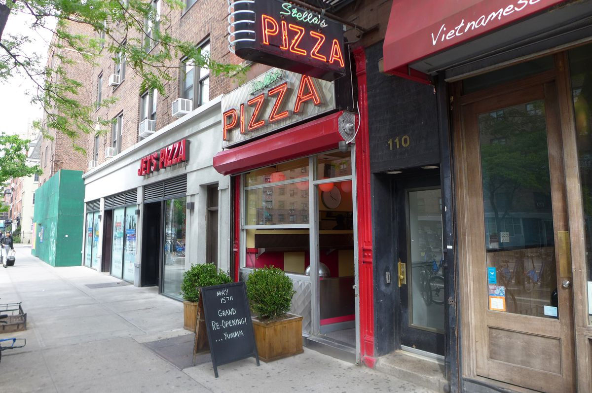 The exterior of a pizza parlor with a Deco neon sign.