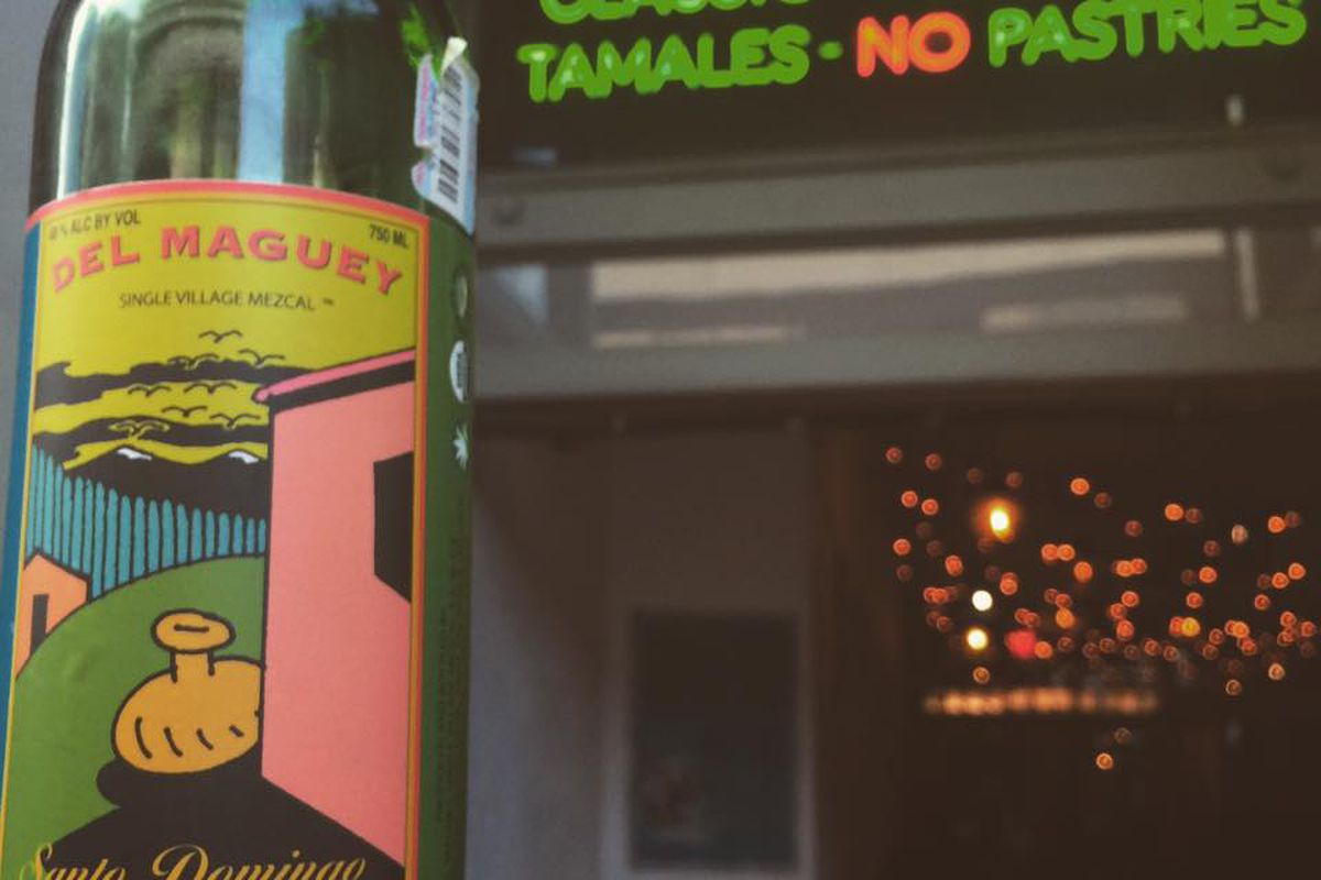 """a bottle of mezcal in front of a neon sign that reads """"tequila, mezcal, tamales, classic cocktails, NO pastries"""""""